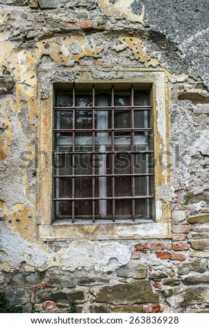 Window on an old European building with wrought iron bars. - stock photo