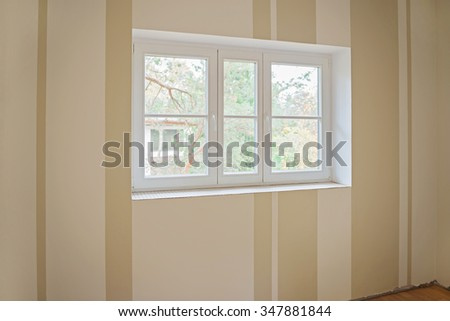 Window on striped wall during house renovation - stock photo
