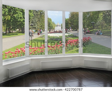 window overlooking the city park with tulips where people have a rest