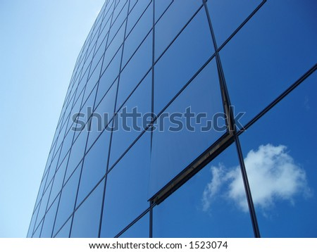 Window panels on a office building in the city with reflection of blue sky