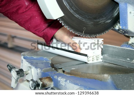 Window Profile Cutting Machine. Worker cutting PVC profile with circular saw. Selective focus. - stock photo