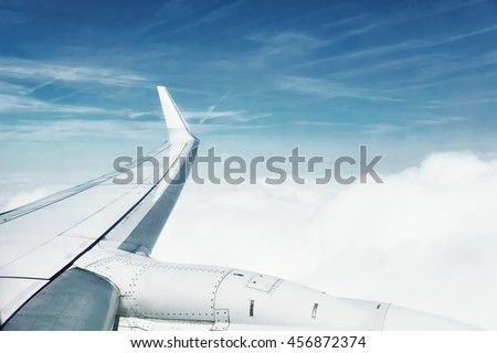 Window view from a flying plane, wing view, blue sky and white clouds