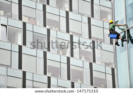 Window washer working high up on modern office building - stock photo
