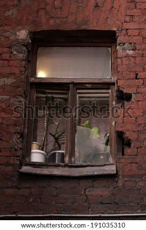 Window with a burning lamp in dark courtyard