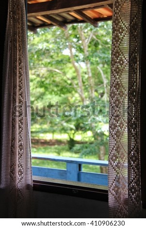 Window with a crochet curtain - stock photo
