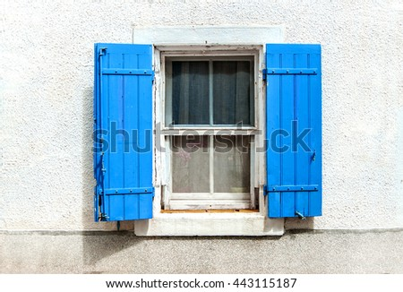 window with blue shutters on white wall background