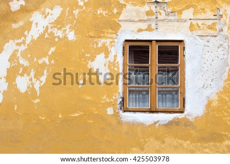 Window with brown frame on the background of the old yellow destroyed wall