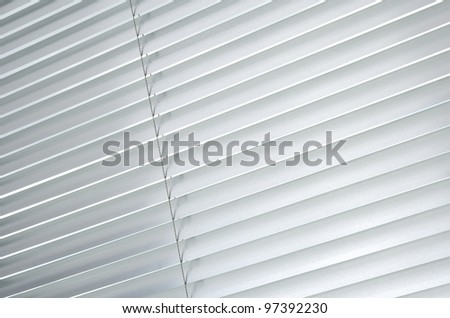 Window with closed metallic blinds, view from inside.