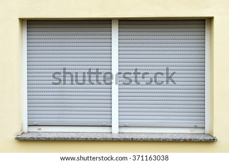 Window with closed roller shutter / Roller shutter - stock photo