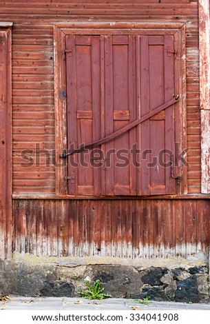 Window with closed shutters, wooden plank wallbackground - stock photo