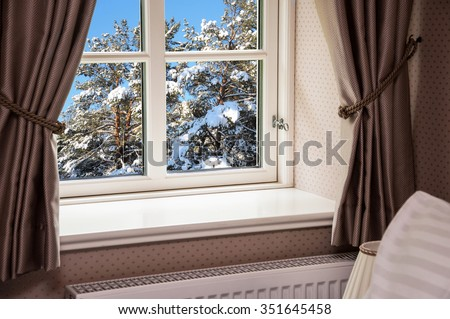 Window with curtains in winter