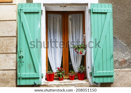 Window with flowers in typical houses in southern France, Provence - stock photo