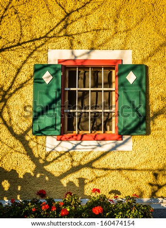 Window with green shutters and decorative tree shadow on a wall.Styria,Austria. - stock photo