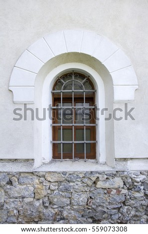 Window with iron bars on the old church.