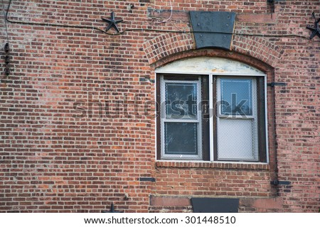 Window with metal grid in an old brick building in Brooklyn