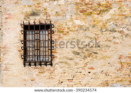 Window with Old Grating - Italy / Detail of a window with an old and rusty grating on a old wall with bricks. San Gimignano, Siena, Tuscany, Italy - stock photo
