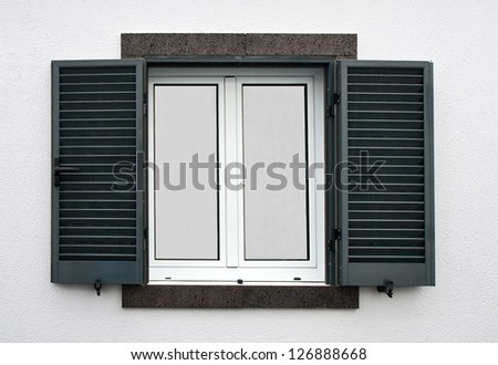 Window with open shutters on a white stone wall - stock photo