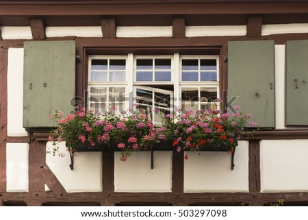 Window with pink geranium and green shutters in a half timber house with red wooden beams.