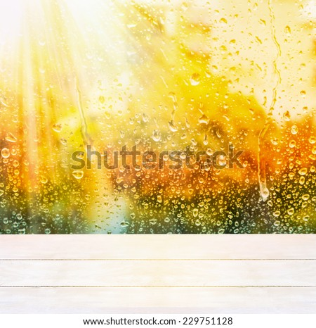 Window with raindrops and white wooden sills, autumn background  - stock photo