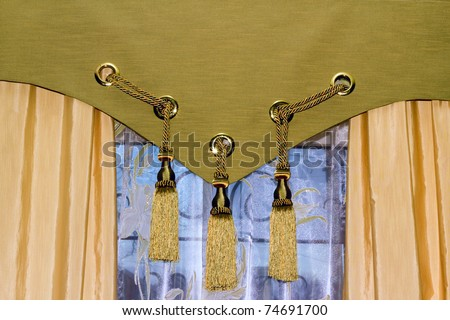 window with tulle and decorated with tasselled curtains