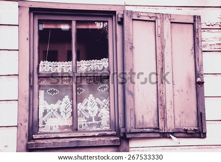 Window with white lace curtain decorated with windmill and tree pattern and wooden hinged shutters . (Amiens, Picardy, France)  Rustic background. Toned photo. - stock photo