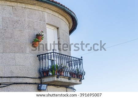 Window with wrought iron balcony and flower pots in Cambados