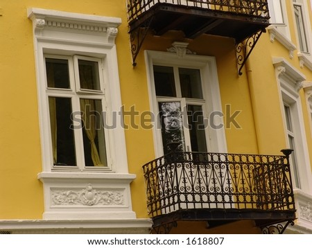 Windows and balcony. A beautiful yellow classic building - downtown Bergen, Norway