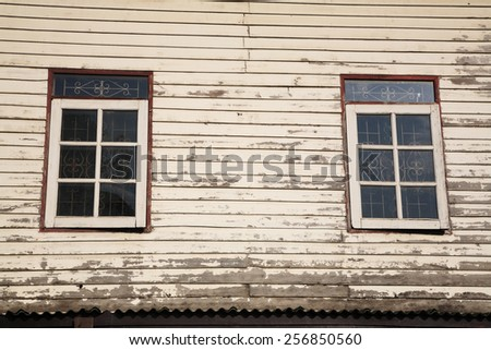 Windows and old wooden wall of cottage in Thai countryside - stock photo