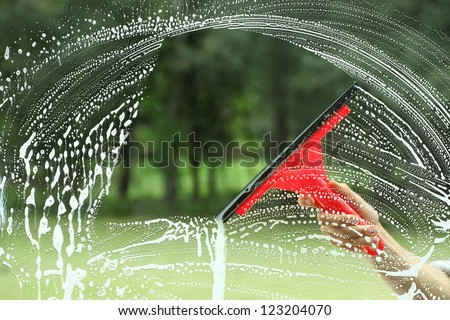 Windows cleaning, glass without smudges red squeegee - stock photo