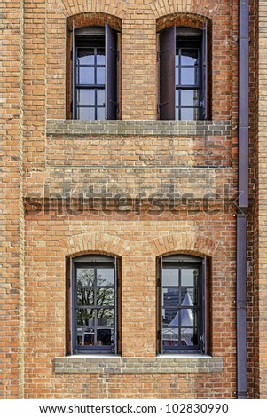 Windows in a red brick wall - stock photo