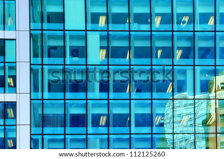Windows of a modern office building with reflections - stock photo