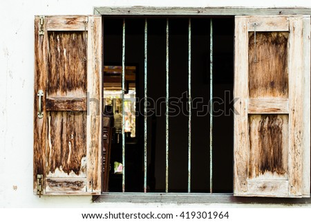 Windows of an old house, are designed to widely open for maximum ventilation. Steel bars protect the house from risks. This window design is common in Thailand, and generally seen in the countryside.