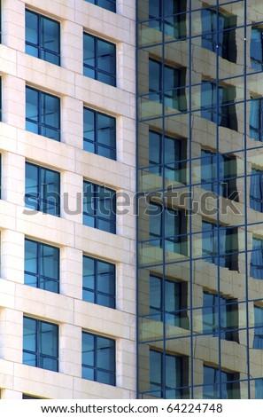windows reflecting in modern building - stock photo