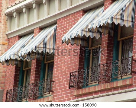 Windows with awnings on brick building - stock photo