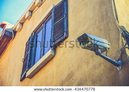 windows with cctv on wall (Vintage filter effect used) - stock photo