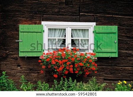 Windows with flower decoration in textured wooden wall - stock photo