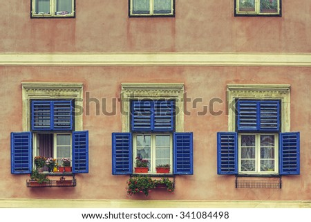 Windows with wide open blue wooden shutters and decorative blooming flowers in pots.