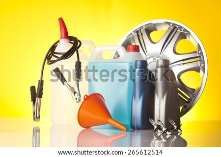 windshield washer fluid,motor oil and alloy wheel isolated on yellow background - stock photo