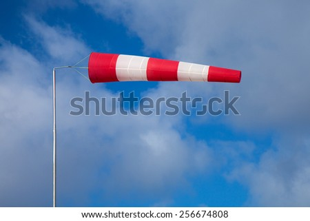 windsock indicating strong wind on blue sky with light clouds background - stock photo