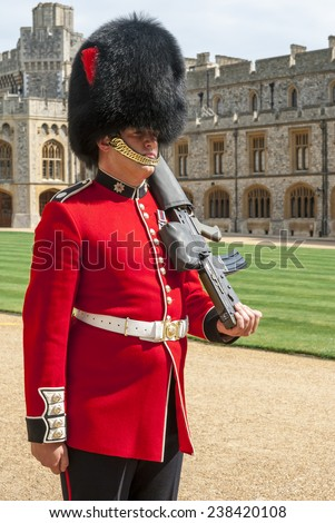 WINDSOR, ENGLAND - JULY 26: Royal Guard holding gun on duty in Windsor Castle, one of the official residences of the British Royal Family. - stock photo