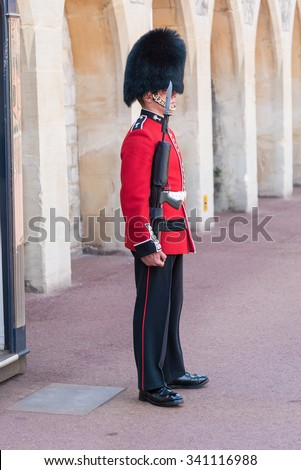WINDSOR, ENGLAND - JULY 24: Royal Guard holding gun on duty pictured on July 24th, 2015, in Windsor Castle, Windsor, UK. Windsor castle is one of the official residences of the British Royal Family. - stock photo