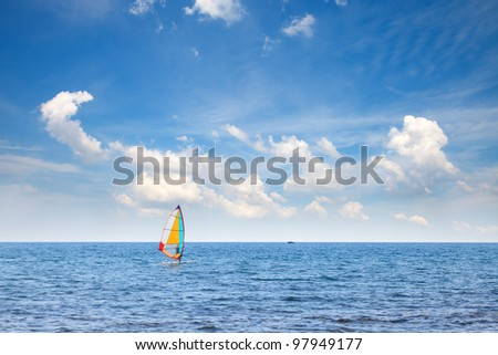 Windsurfer in the sea under a blue sky with clouds