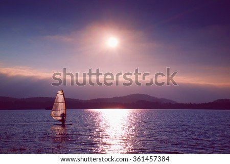 Windsurfer leans back into breeze Shot with gentle filter. Strong sun makes reflections in mirror of water level. Vivid effect. - stock photo