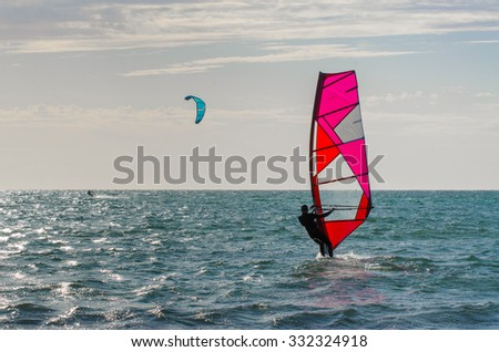 Windsurfer on surfboard slides on waves sea waterfront activity at the beach - stock photo