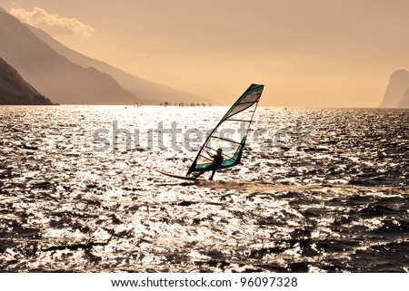 windsurfer panorama silhouette against a sparking  lake of Garda, in Trentino. Italy - stock photo