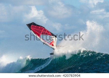Windsurfer rides among the huge tubes and waves of the Indian Ocean on the island of Mauritius - stock photo