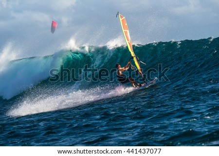 Windsurfer rides among the huge tubes and waves of the Indian Ocean on the island of Mauritius