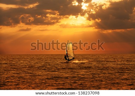 Windsurfer sailing in the sea at sunset  - stock photo