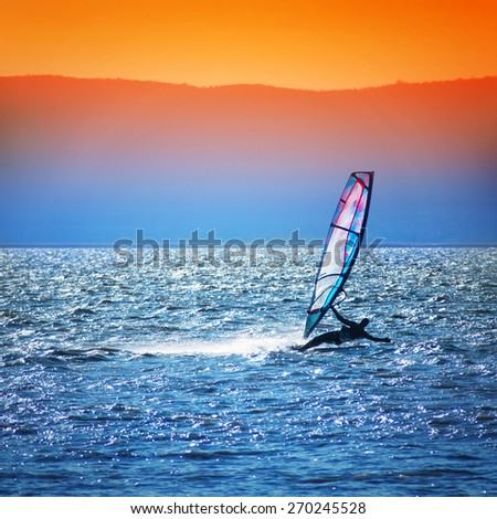 Windsurfer silhouette against a sunset background - stock photo