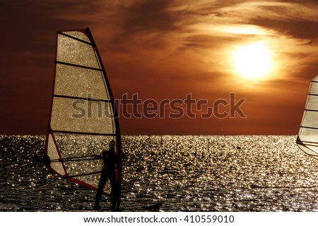 windsurfer silhouette against a sunset background. Natural sky - stock photo